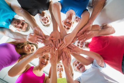 36424851 - low angle view of fit people stacking hands at health club